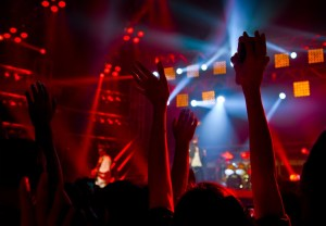 Disco party concert with large group of happy dancing people, silhouette of hands up in the air over blur red colorful stage lights, active lifestyle entertainment, music nightclub, night life concept